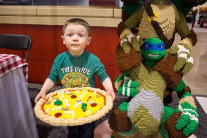 A boy shows off the block pizza he put together with his relay team at LEGO KidsFest in Novi, Mich. on April, 27 2014.  (credit: George Fox/CW50)