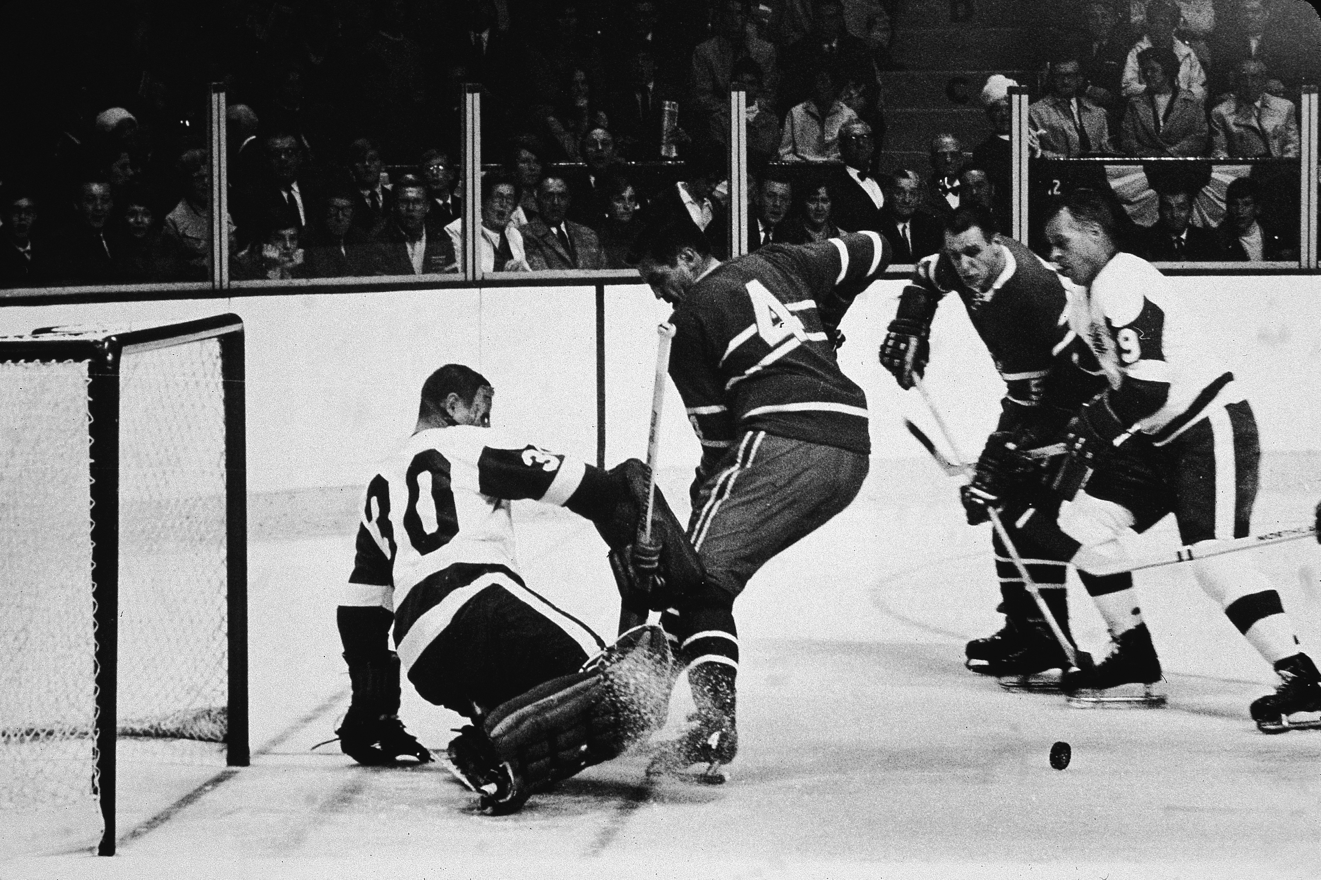 MONTREAL, QC - NOVEMBER 8: Goalie Terry Sawchuk #30 of the Detroit Red Wings makes the save on the shot by Jean Beliveau #4 of the Montreal Canadiens as Gordie Howe #9 of the Red Wings watches on November 8, 1968 at the Montreal Forum in Montreal, Quebec, Canada. (Photo by Hulton Archive/Getty Images)